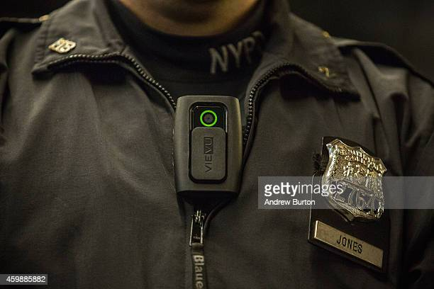 New York Police Department Officer Joshua Jones demonstrates how to use and operate a body camera during a press conference on December 3 2014 in New...
