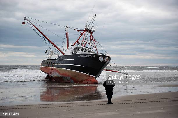 New York Police Department officer looks at an aground fishing vessel on the shore of Rockaway Beach on February 25 2016 in Queens NY The fishing...