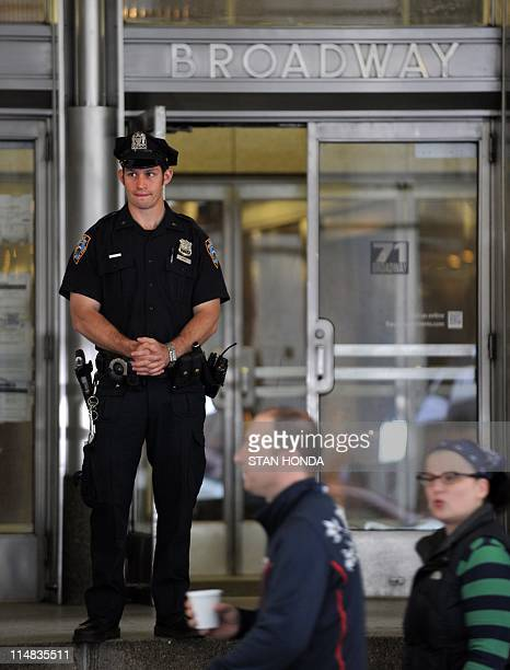 A New York Police Department officer stands guard at the entrance to the building where former IMF head Dominique StraussKahn is being held under...