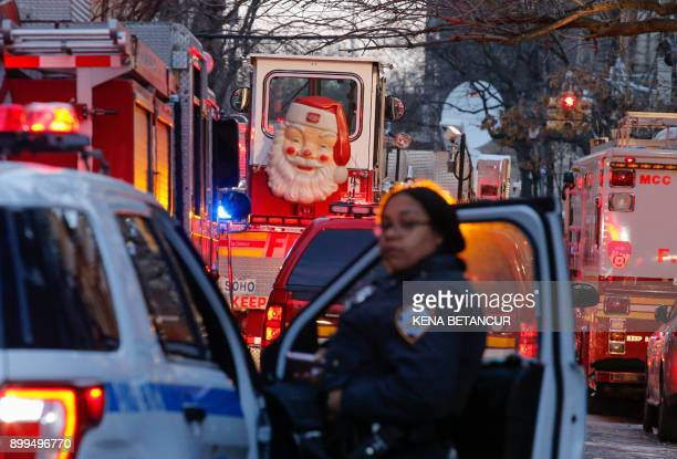 A New York Police Department officer works on the scene of an apartment fire on December 29 2017 in the Bronx borough of New York City Officials said...