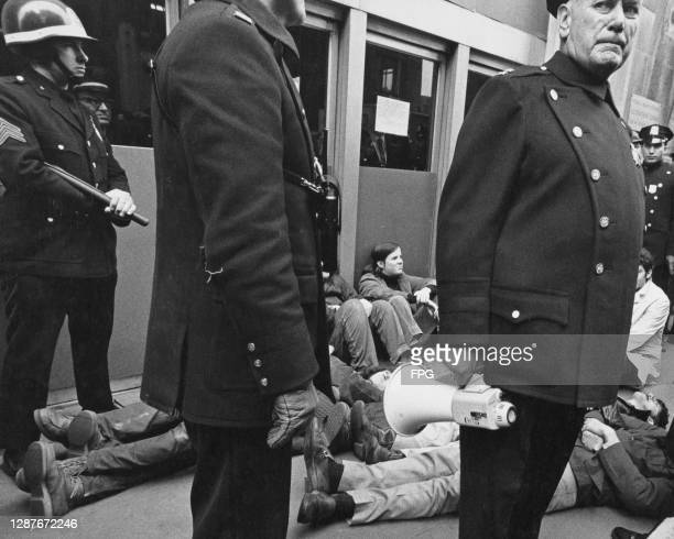 New York Police Department officers monitor a sit-in protest at an unspecified location in New York City, New York, circa 1975.