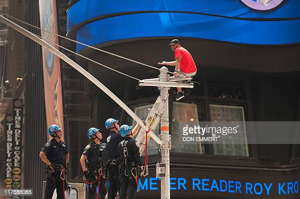 New York Police Department officers negotiate with a man on top of a stoplight pole inTimes Square June 28 2011 in New York Times Square was closed...