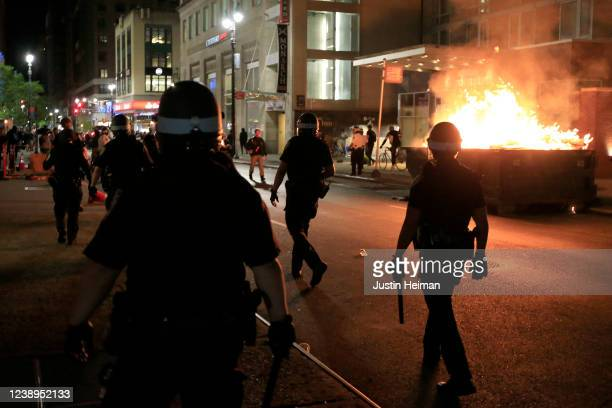 New York Police Department officers walk past a dumpster fire in front of the Hampton Inn on west 35th street during a rally in response to the death...