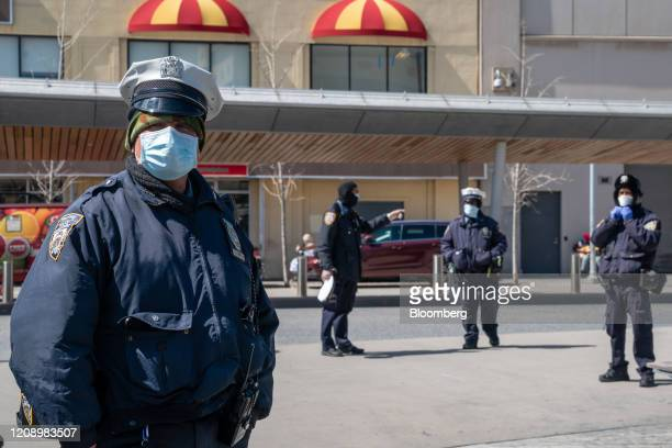 New York Police Department officers wear protective masks at the Fordham bus hub in the Bronx borough of New York, U.S., on Thursday, April 2, 2020....