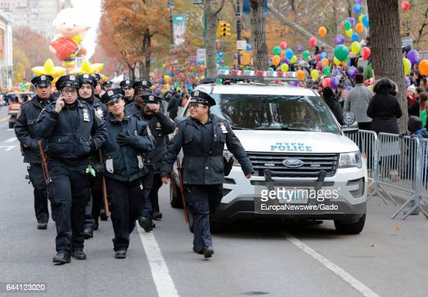 New York Police Department officers with riot gear walk past a police cruiser with colorful balloons visible in the background during the 90th Macys...