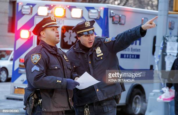New York Police Department officers work on the scene of an apartment fire on December 29 2017 in the Bronx borough of New York City Officials said...