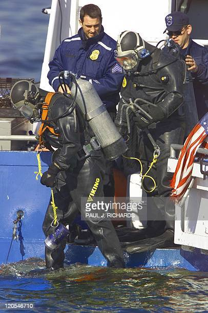 New York Police Department scuba team members jump into Jamica Bay from a NYPD boat 13 November 2001 to search for the missing flight data recorder...