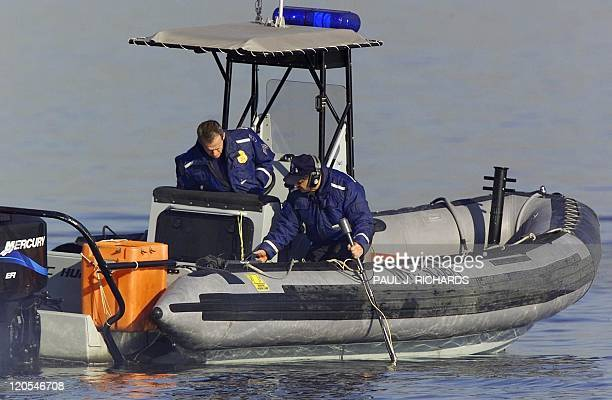 New York Police Department Scuba Team members Sgt John Cummings and Detective Alan Kane adjust and listen to a Ping Locater 13 November 2001 as they...