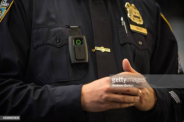 New York Police Department Sergeant Joseph Freer demonstrates how to use and operate a body camera during a media press conference on December 3,...
