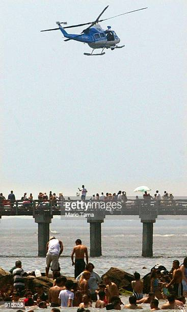 New York police helicopter patrols over beachgoers at Coney Island July 4 2002 in the Brooklyn borough of New York City Security has been tightened...