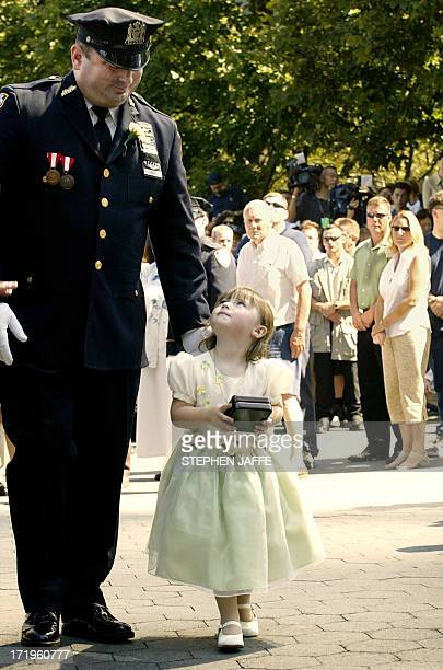 New York Police officer James Smith escorts his 2-year-old daughter Patricia as she carries her mother's police badge during a ceremony for the...