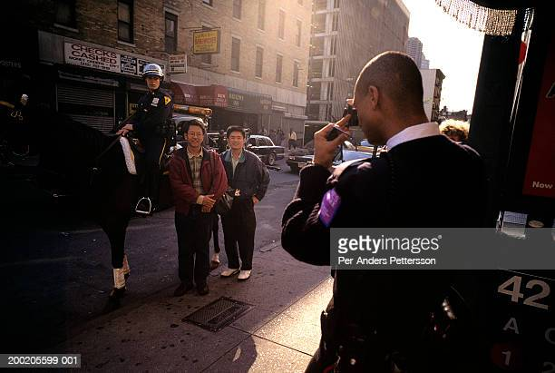 new york police officer on horse pose for pictures with asian tourists in times square - per-anders pettersson stock pictures, royalty-free photos & images