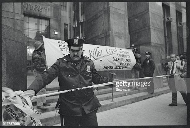 Police officer places a cordon around the entrance to criminal courts building where demonstrators protested the acquittal of six transit police...