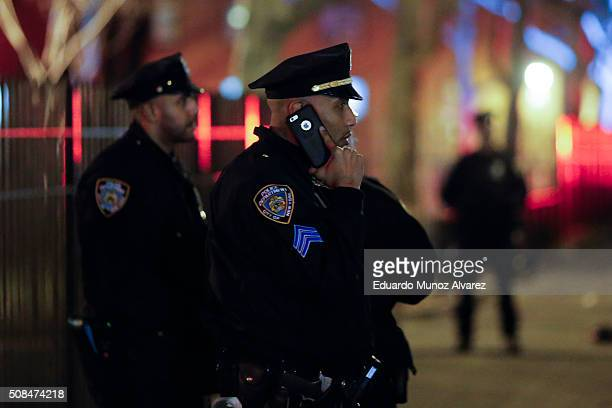 New York Police Officer talks by phone near the scene of a shooting on February 4 2016 in the Bronx in New York City Two NYPD officers were shot on...