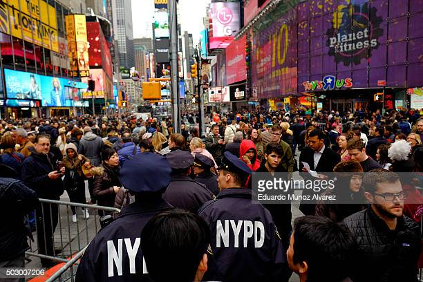 New York Police Officers patrol on foot and keep an eye on people at Times Square before New Year's Eve celebrations on December 31 2015 in New York...