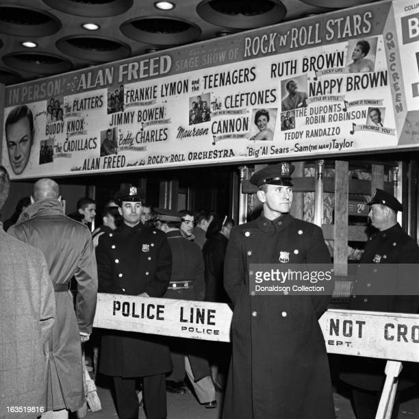 New York police officers stand around a gate that reads Police Line Do Not Cross in under the marquee that reads In Person Alan Freed heading a Stage...