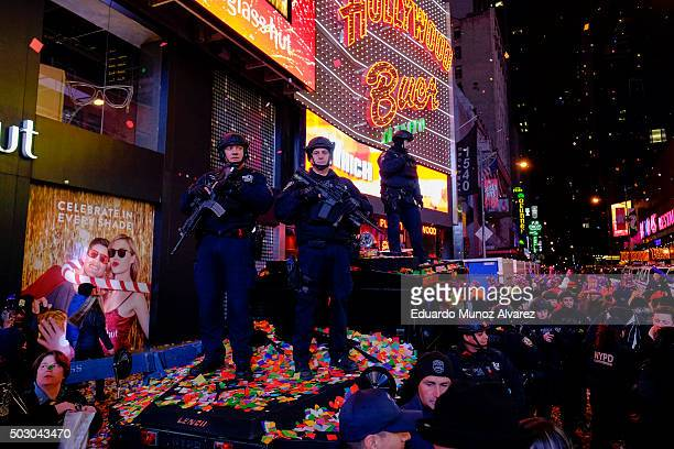 New York Police Officers stand guard as confetti is seen on the air while people take part during New Year's Eve celebrations at Times Square on...
