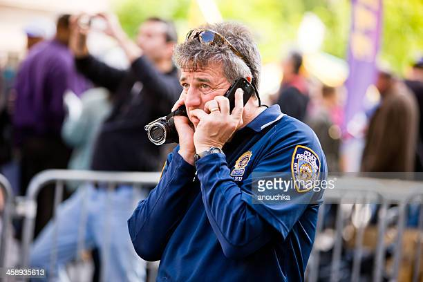 new york-polizisten am telefon, hält video camera - video call stock-fotos und bilder