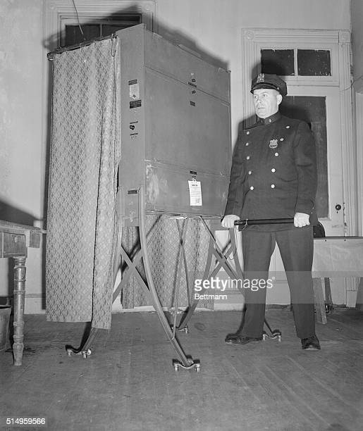 Polls Guarded Patrolman Joseph Novak stands guard over a voting machine in a barber shop in New York City Nov 3rd after the polls were ordered seized...