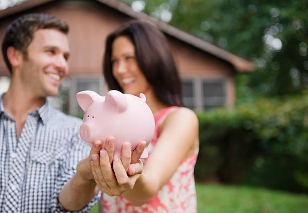 USA, New York, Putnam Valley, Roaring Brook Lake, Couple holding piggy bank