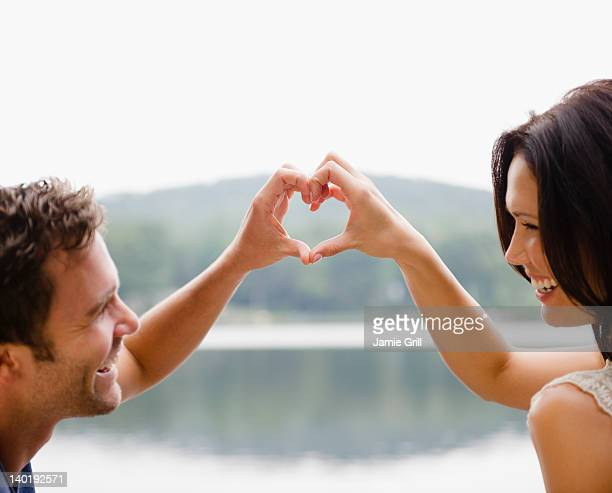 USA, New York, Putnam Valley, Roaring Brook Lake, Couple making heart shape with hands