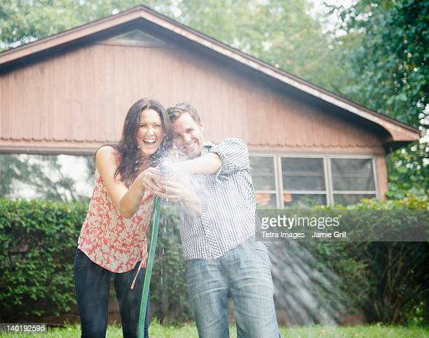 USA, New York, Putnam Valley, Roaring Brook Lake, Couple playing with hose