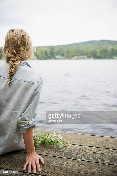 USA, New York, Putnam Valley, Roaring Brook Lake, Rear view of woman sitting on pier by lake