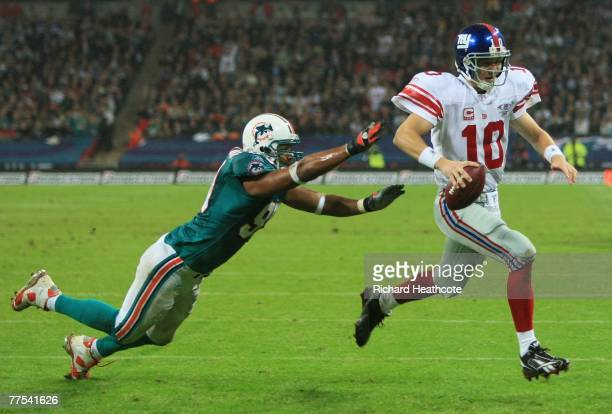 New York quarterback Eli Manning outpaces Jason Taylor of the Dolphins to score the opening touchdown during the NFL Bridgestone International Series...