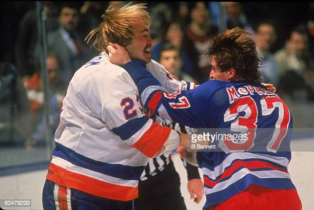 New York Ranger George McPhee grabs a handful of hair during a fight against Bobby Nystrom of the rival NY Islanders at Nassau Coliseum Uniondale New...