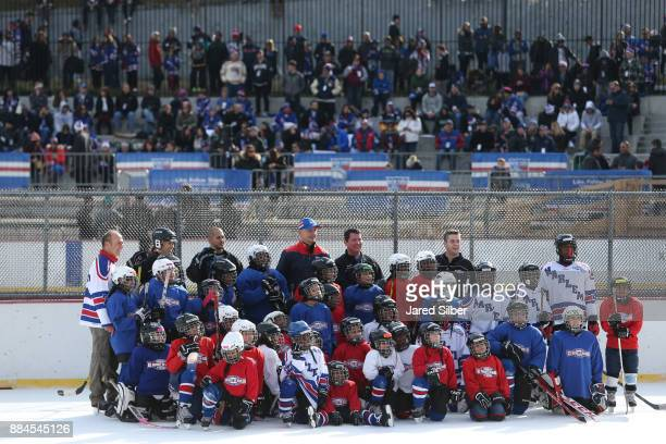New York Rangers Alumni Adam Graves poses for a group picture with kids from Ice Hockey In Harlem during the New York Rangers youth hockey clinic...