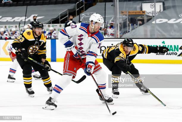 New York Rangers center Kevin Rooney gets past Boston Bruins left wing Brad Marchand and Boston Bruins left defenseman Matt Grzelcyk during a game...
