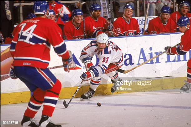 New York Rangers center Mark Messier plays the puck away from Montreal Canadiens right wing Mark Recchi as Canadiens defenseman Peter Popovic looks...