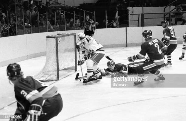 New York Rangers' center Mark Pavelich L gets the puck past goalie Roland Melanson of the New York Islanders to score in the second period of their...