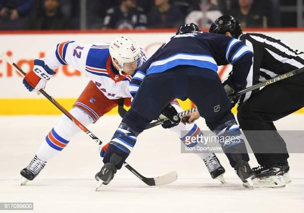 New York Rangers Center Peter Holland and Winnipeg Jets Center Matt Hendricks face off during a NHL game between the Winnipeg Jets and New York...