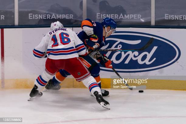 New York Rangers Center Ryan Strome checks New York Islanders Center Mathew Barzal into the boards as they battle for the puck during the third...