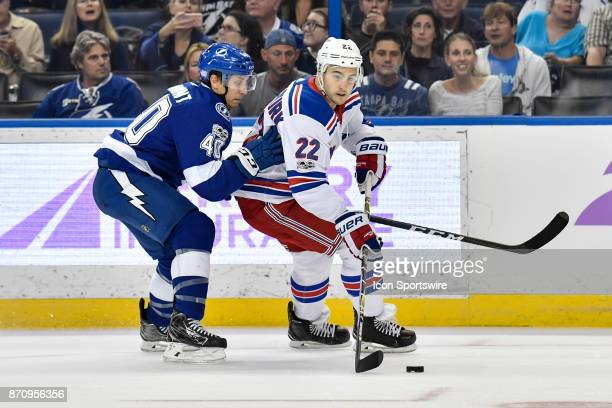 New York Rangers defender Kevin Shattenkirk is closely defended by Tampa Bay Lightning center Gabriel Dumont during the first period of an NHL game...