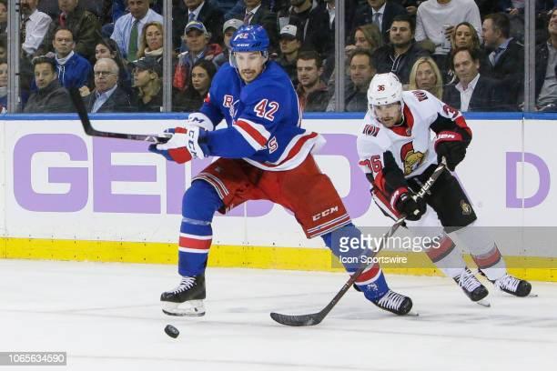 New York Rangers defenseman Brendan Smith and Ottawa Senators center Colin White fight for loose puck during the Ottawa Senators and New York Rangers...