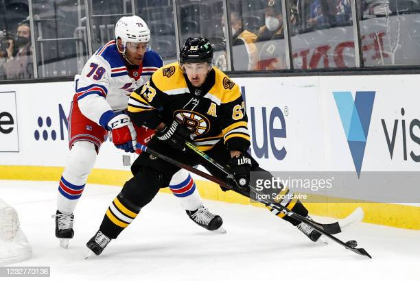 New York Rangers defenseman K'Andre Miller defends on Boston Bruins left wing Brad Marchand during a game between the Boston Bruins and the New York...