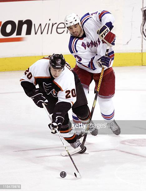 New York Rangers defenseman Michal Rozsival battles Philadelphia Flyers center RJ Umberger for the puck at the Wachovia Center in Philadelphia...
