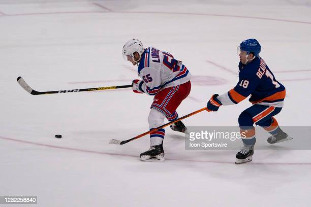 New York Rangers Defenseman Ryan Lindgren chases the puck with New York Islanders Left Wing Anthony Beauavillier in pursuit during the third period...