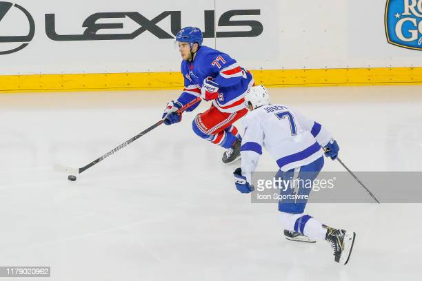 New York Rangers defenseman Tony DeAngelo skates with the puck and looks to pass as Tampa Bay Lightning right wing Mathieu Joseph closes in to defend...