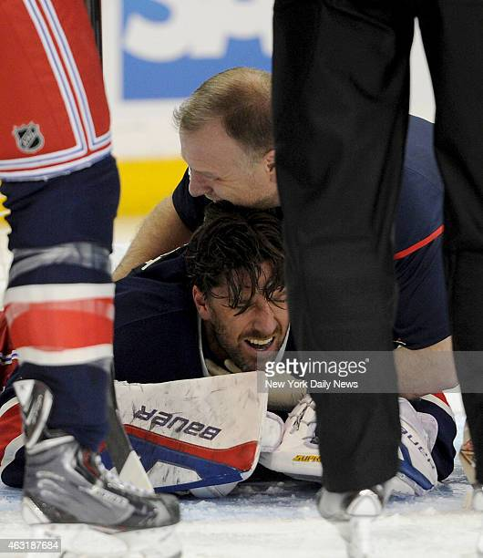 New York Rangers goalie Henrik Lundqvist gets tended to after having stick hitting him under the neck during the second period when the New York...