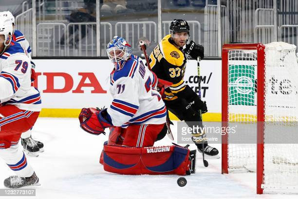 New York Rangers goalie Keith Kinkaid and Boston Bruins center Patrice Bergeron watch the puck trickle wide during a game between the Boston Bruins...