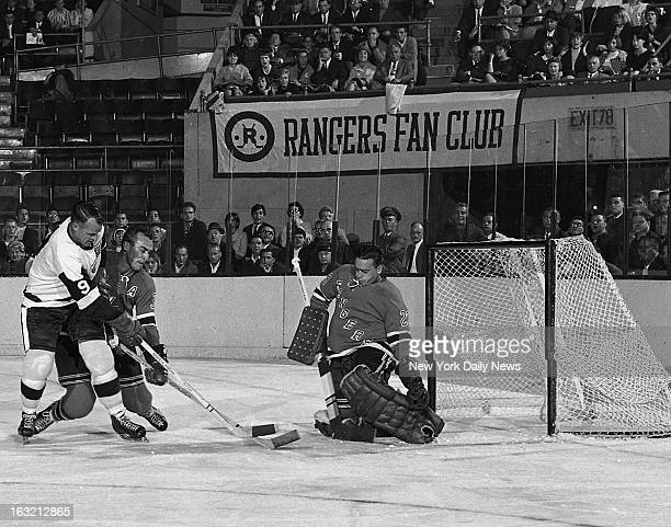 New York Rangers' goalie Marcel Paille smothers shot by Detriut Red Wings' Gordie Howe who is tied up by defenseman Harry Howell after firstperiod...