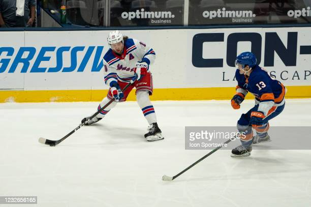 New York Rangers Left Wing Artemi Panarin passes the puck with New York Islanders Center Mathew Barzal defending during the second period of the...