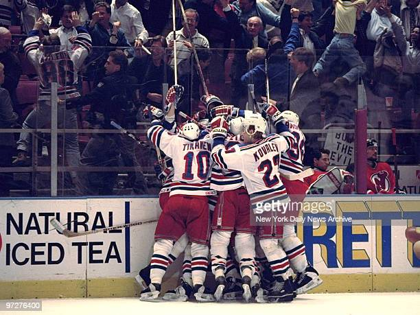 New York Rangers' Stephane Matteau is mobbed by teammates after his goal at 424 of the second overtime period gives the Rangers' a 21 win over the...