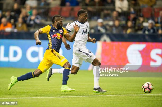 New York Red Bulls defender Kemar Lawrence an Vancouver Whitecaps forward Alphonso Davies race to the ball during the CONCACAF Champions League...