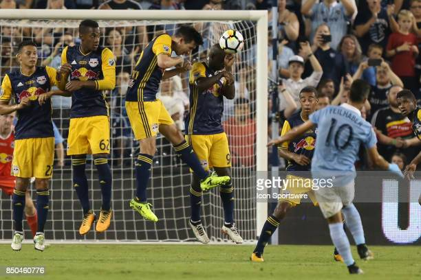 New York Red Bulls defender Kemar Lawrence takes a free kick from Sporting Kansas City midfielder Benny Feilhaber off the head in the first half of...