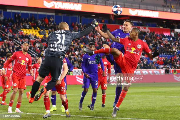 New York Red Bulls goalkeeper Luis Robles punches the ball away from Orlando City defender Shane O'Neill and New York Red Bulls defender Kyle Duncan...