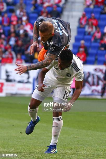 New York Red Bulls midfielder Daniel Royer falls over the top of Chicago Fire midfielder Mo Adams during the first half of the Major League Soccer...